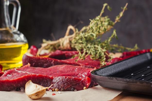 Tranches de viande crue fraîche, steaks de bœuf et poêle à frire, gros plan