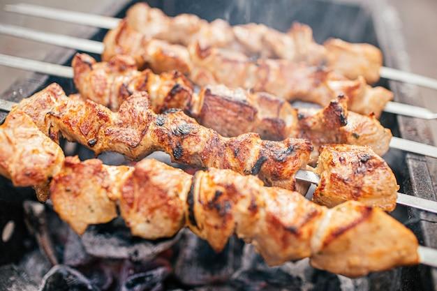 Des tranches de viande juteuses avec sauce se préparent sur du shish kebab au feu. barbecue extérieur.