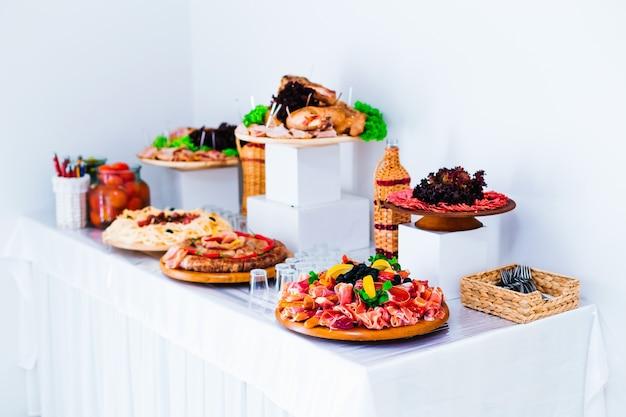 Tranches de viande de porc de boeuf sur des assiettes en bois et réception de mariage de boisson