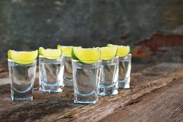 Tranches de vodka et de lime sur fond en bois.