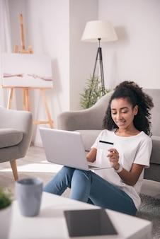 Transaction d'argent en ligne. belle belle femme regardant sa carte de crédit tout en faisant une transaction d'argent en ligne