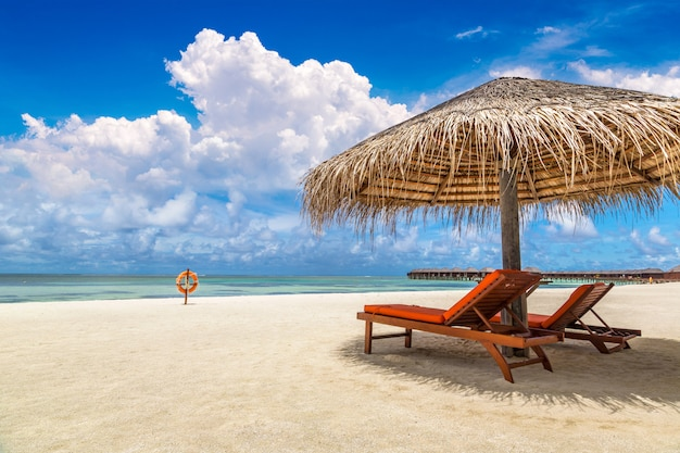Transat et parasol en bois sur la plage tropicale aux maldives