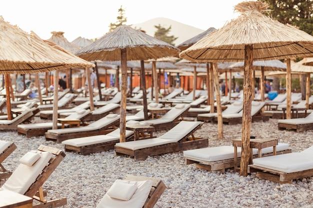 Transats et parasols en paille sur une plage de galets