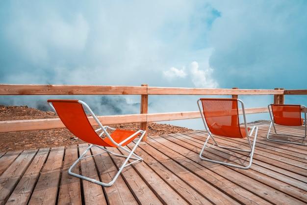 Transats rouges debout sur une terrasse en bois dans les alpes nuageuses