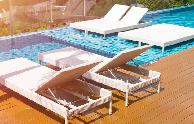 Transats vides au bord de la piscine bleue pendant la pandémie, coronavirus. fond tonique, texture