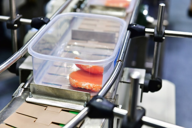 Transfert de boîtes de produits alimentaires de la viande crue sur des systèmes de convoyeurs automatisés