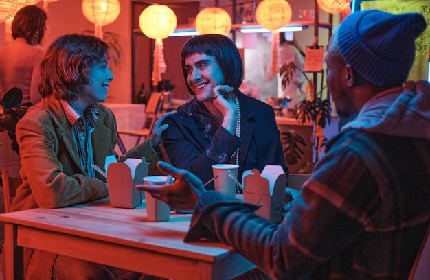 Transgenre assis à table avec ses amis et leur parlant lors d'une réunion au bar
