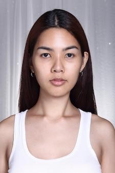 Transgenre femme asiatique avant maquillage coiffure brune. pas de retouche, visage frais avec une peau agréable et lisse. studio éclairage fond gris, portrait