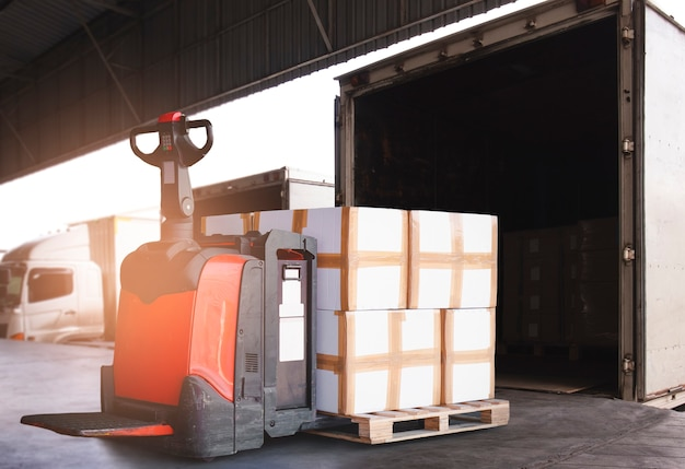 Transpalette électrique pour chariot élévateur avec pile de caisses de chargement déchargées dans un camion porte-conteneurs. expédition de fret par camion.