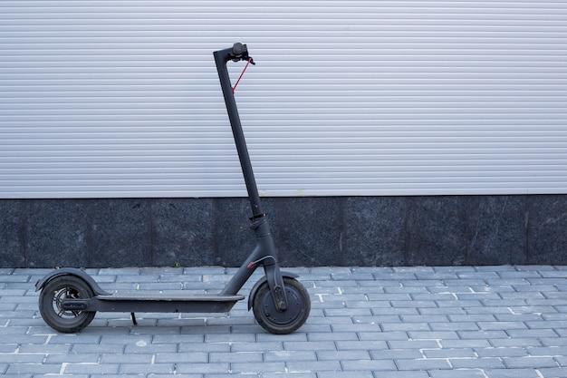 Transport électrique écologique, technologie moderne, scooter électrique près du mur gris