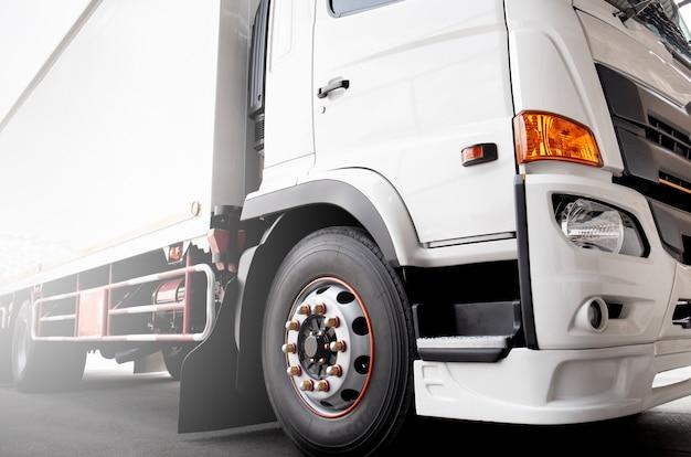Transport de marchandises, parage de camions blancs.
