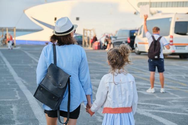 Transport maritime, port méditerranéen, mère de famille voyageuse et petite fille marchant ensemble tenant la main