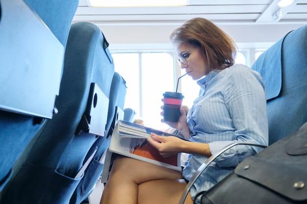 Transport de passagers, femme assise dans la cabine du ferry de mer confortable