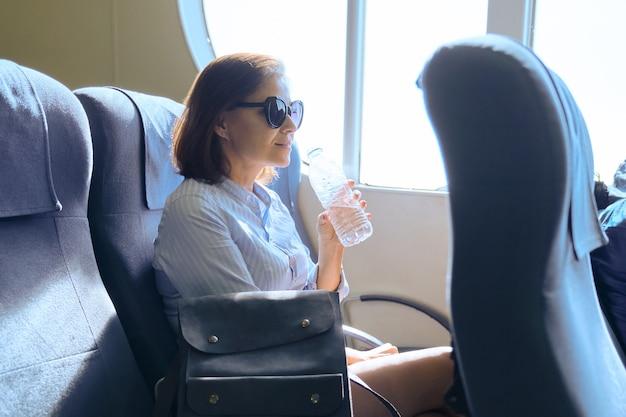 Transport de passagers, femme assise à l'intérieur d'un ferry de mer confortable