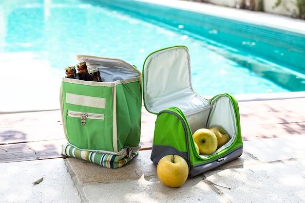 Transportant des sacs portables réfrigérateurs pour la nourriture et les boissons. pique-nique au bord de la piscine