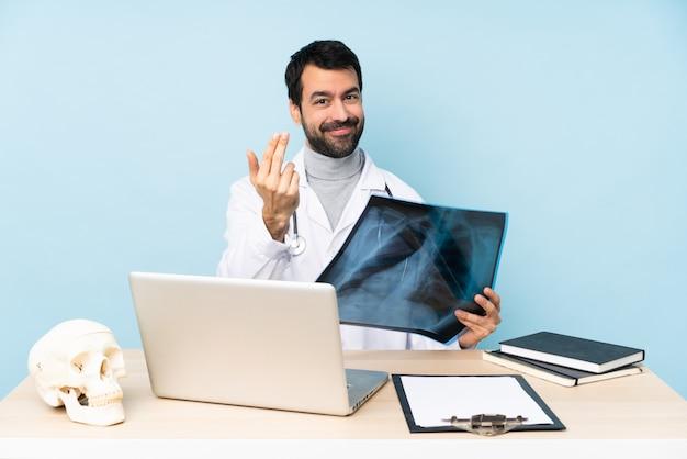 Traumatologue professionnel en milieu de travail invitant à venir avec la main.