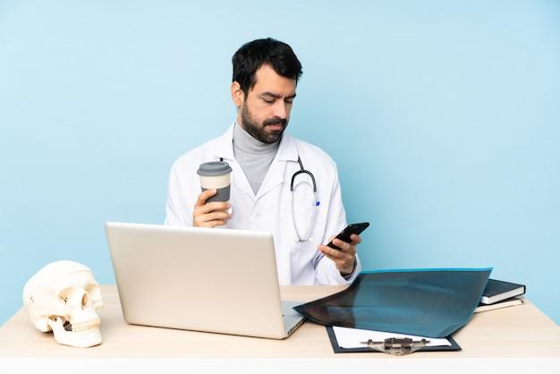 Traumatologue professionnel en milieu de travail tenant un café à emporter et un mobile