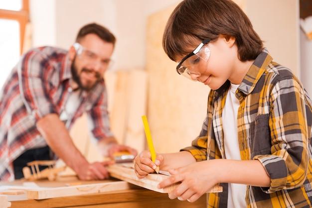 Le travail acharné est la clé du succès. souriant petit garçon faisant des mesures sur la planche de bois tout en travaillant avec son père en atelier