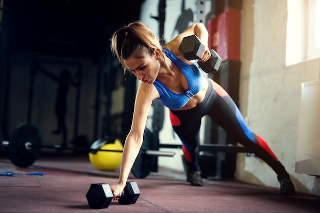 Travail acharné des femmes au gymnase avec des haltères push ups. femme forte au gymnase.