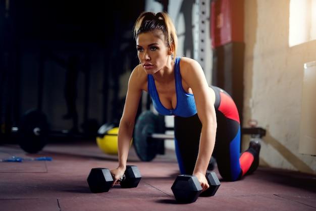 Travail acharné des femmes au gymnase avec des haltères push ups. femme forte à
