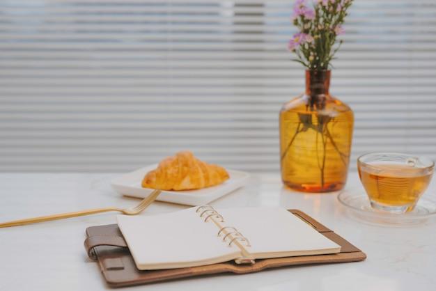 Travail d'affaires sur le café de table de marbre avec la boulangerie de croissant