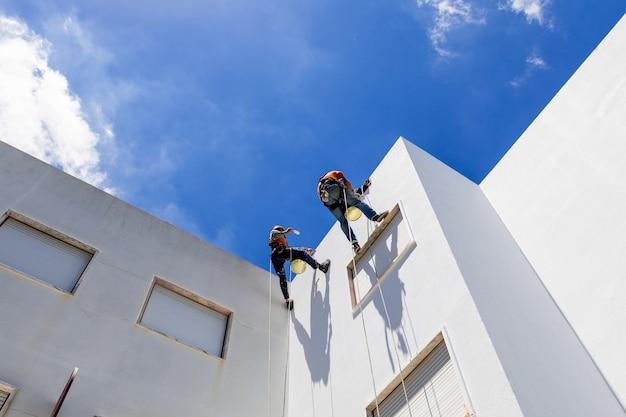 Travail alpiniste industriel sur mur blanc