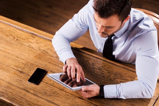 Travail au comptoir du bar. vue de dessus d'un jeune homme confiant en chemise et cravate travaillant sur une tablette numérique alors qu'il était assis au comptoir du bar