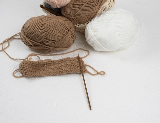 Travail au crochet avec crochet en bois et boule de fil marron,