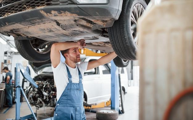 Travail bien fait. l'employé en uniforme de couleur bleue travaille dans le salon automobile.