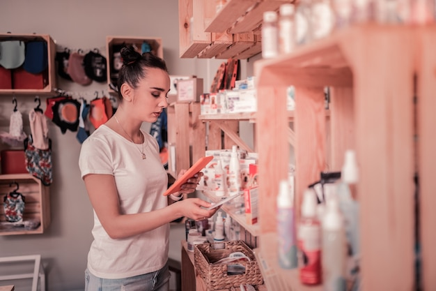 Travail en boutique. femme aux yeux noirs portant un t-shirt blanc se sentant occupée à travailler dans une boutique pour animaux de compagnie