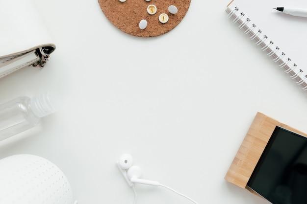 Travail de bureau, concept plat de l'éducation avec désinfectant, clips, téléphone, écouteurs, crayon et bloc-notes et sac à main pour dames sur fond blanc.