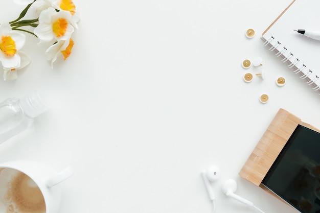 Travail de bureau, éducation concept plat laïc avec clips, téléphone, écouteurs, tasse de café, crayon et bloc-notes et fleurs de tulipes sur fond blanc.