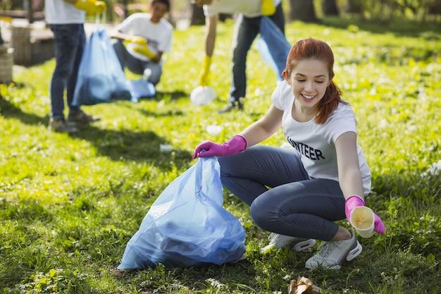 Travail communautaire. adorable femme bénévole souriant tout en ramassant des ordures