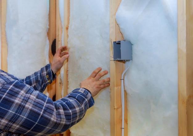 Travail composé d'isolation en laine minérale dans l'isolation thermique de chauffage mural maison chaude,