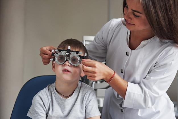 Travail en cours. enfant assis dans le cabinet du médecin et avoir testé son acuité visuelle.