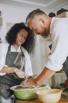 Travail créatif mutuel. couple élégant adulte dans des vêtements décontractés et des tabliers. les gens créant un bol sur un tour de poterie dans un studio d'argile.
