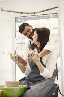 Travail créatif mutuel. couple élégant dans des vêtements décontractés et des tabliers. les gens créant un bol sur un tour de poterie dans un studio d'argile.