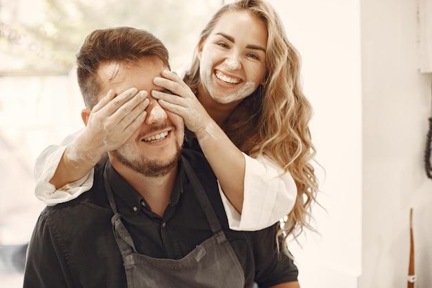 Travail créatif mutuel. jeune beau couple en vêtements décontractés et tabliers. les gens créant un bol sur un tour de poterie dans un studio d'argile.