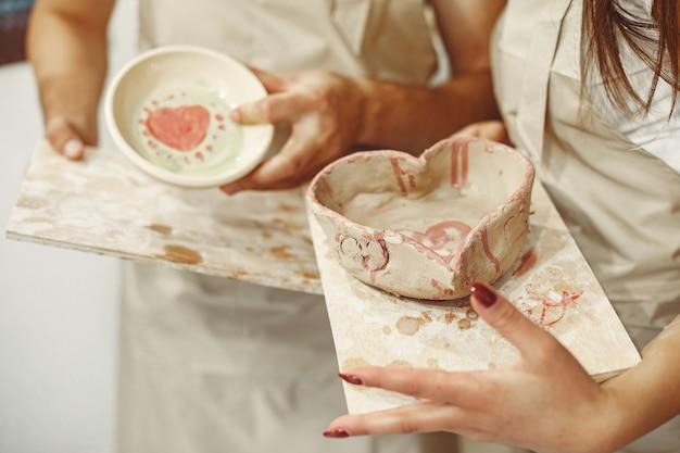 Travail créatif mutuel. jeune beau couple en vêtements décontractés et tabliers. les gens tiennent des plats en céramique.
