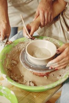 Travail créatif mutuel. mains créant un bol sur un tour de poterie dans un studio d'argile.