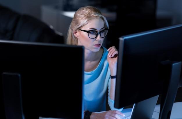Travail dangereux. programmeur habile impliqué et intelligent assis au bureau et utilisant des ordinateurs tout en travaillant à la résolution des codes de mot de passe en ligne