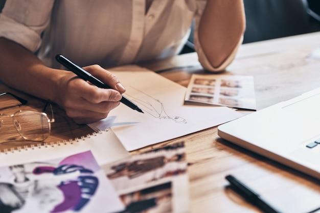 Travail sur des designs tendance. gros plan d'une jeune femme travaillant sur des croquis alors qu'elle était assise dans son atelier