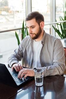 Travail à distance. homme affaires, portable utilisation, caucasien, séance homme, table, dans, café, travailler ordinateur portable, boit eau