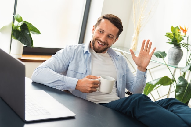 Travail à distance. un pigiste ou un gestionnaire sûr de lui avec des jambes jetées sur une table utilise un ordinateur portable pour communiquer avec les employés. concept d'appel vidéo