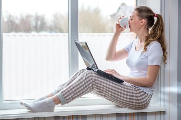 Travail à distance en quarantaine à domicile. protection contre les coronavirus. femme de race blanche à la fenêtre, boire du café tout en travaillant sur l'ordinateur portable.