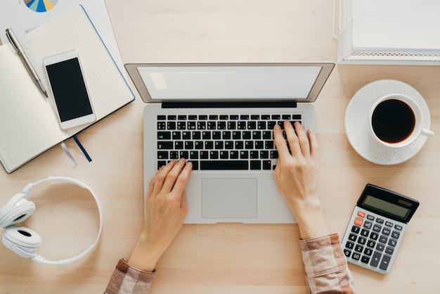 Travail à domicile, apprentissage en ligne. bureau en bois, table. vue de dessus. l'enseignement à distance. mains de femme tapant sur ordinateur portable. freelance, concept nomade numérique