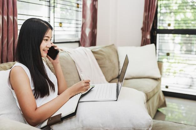 Travail à domicile et concept de magasinage en ligne, femme asiatique d'affaires heureux à l'aide de téléphone mobile et ordinateur portable avec ordinateur portable sur canapé dans le salon à la maison