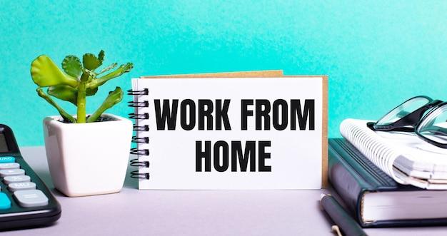 Travail à domicile est écrit sur une carte blanche à côté d'une fleur en pot, d'un agenda et d'une calculatrice. concept organisationnel