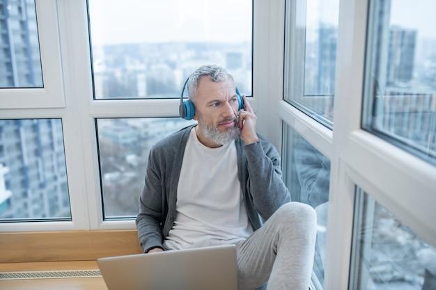 Travail à domicile. un homme mûr avec un ordinateur portable travaillant à domicile et ayant l'air impliqué