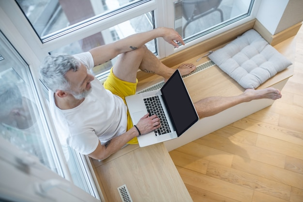 Travail à domicile. un homme en t-shirt blanc assis avec un ordinateur portable et travaillant